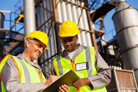 Photo pour Pétrochimiques collaborateurs travaillant à l'usine de raffinage - image libre de droit