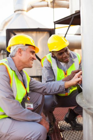 Petrochemical technicians inspecting fuel tank