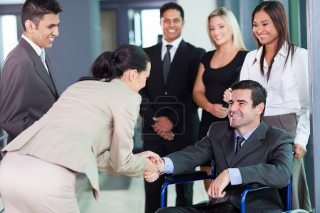 Businesswoman greeting handicapped business partner