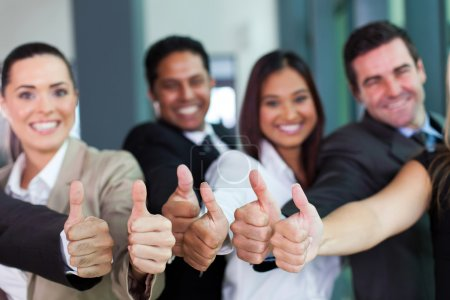 Cheerful business group giving thumbs up...