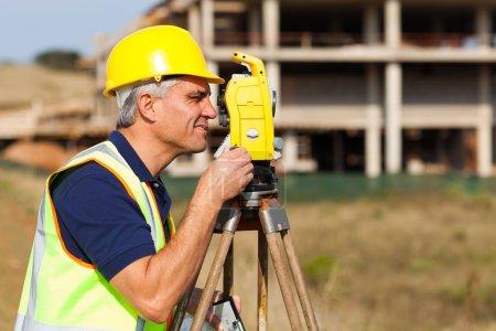 senior land surveyor working with theodolite