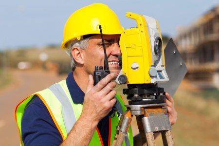 senior land surveyor working with tacheometer