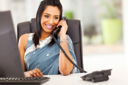 attractive indian receptionist talking on the phone