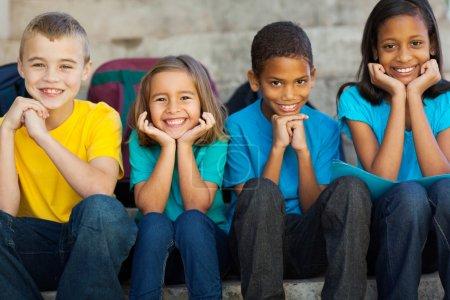 Photo pour Joyeux enfants de l'école primaire assis à l'extérieur - image libre de droit
