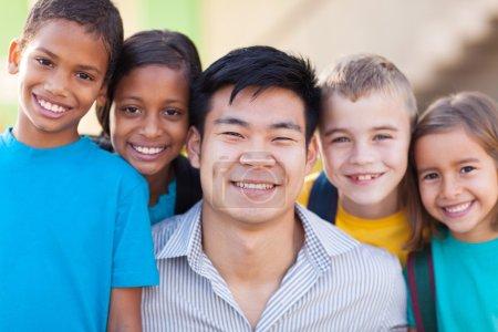 Photo pour Portrait du professeur heureux avec les élèves des écoles primaires de près - image libre de droit