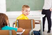 estudiante de escuela primaria mirando hacia atrás en el aula
