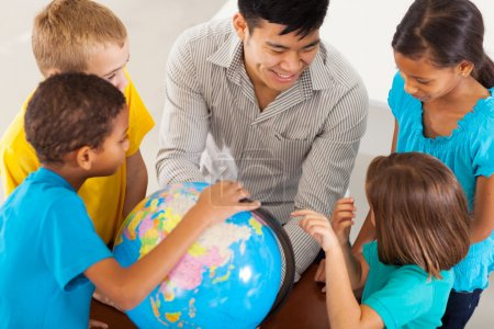 Photo for Cheerful elementary school teacher with a globe teaching geography - Royalty Free Image