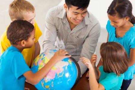 Photo pour Institutrice joyeuse avec un globe enseigner la géographie - image libre de droit