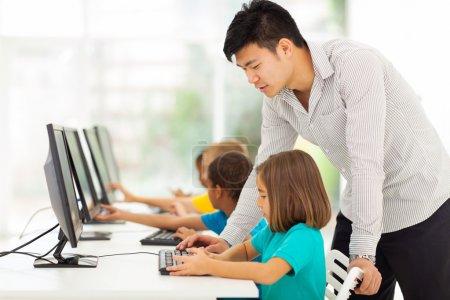 elementary school teacher teaching in computer room