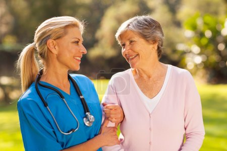 nurse talking to senior woman outdoors