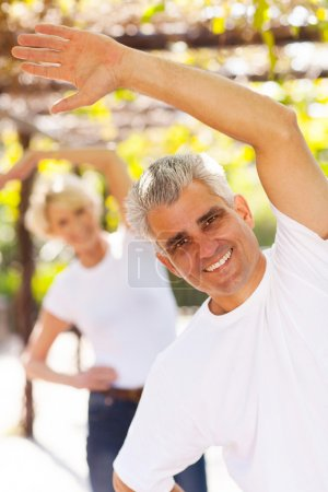 mid age man exercising with wife outdoors