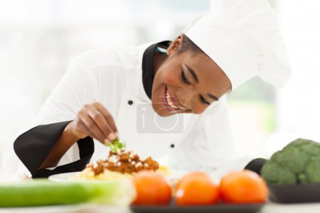 african female chef garnishing spaghetti dish