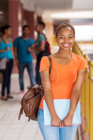 Photo for Happy female African American college student holding books - Royalty Free Image