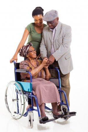 Photo pour Heureux désactivé haute femme africaine avec le mari et sa petite-fille sur fond blanc - image libre de droit