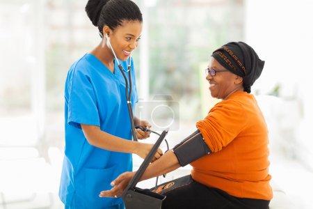 african nurse checking senior patient's blood pressure