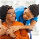 Happy senior patient with friendly female nurse...