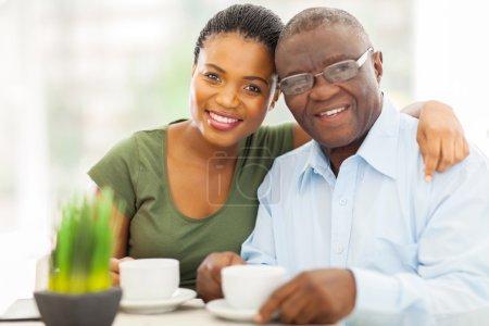 Photo pour Belle jeune fille africaine adulte et père buvant le café à la maison - image libre de droit