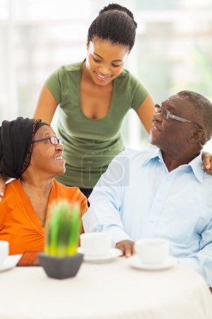 Photo pour Belle fille africaine parler aux parents aînés à la maison - image libre de droit