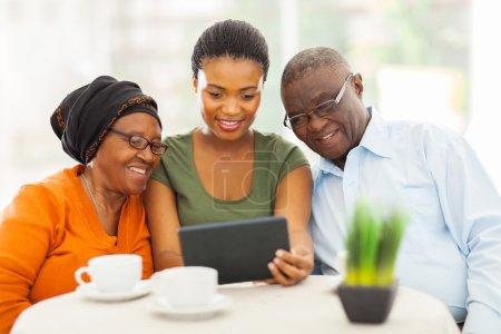 Photo pour Jolie jeune fille africaine adulte avec des parents supérieurs à l'aide de la tablette tactile - image libre de droit