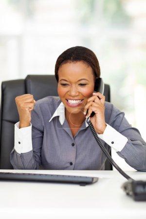 Foto de Feliz joven empresaria afroamericana recibiendo noticias - Imagen libre de derechos