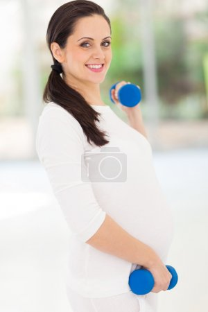 pretty pregnant woman working out with dumbbells