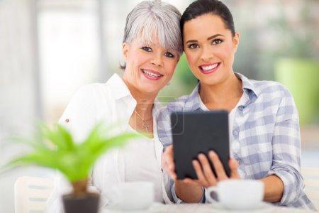 Foto de Hermosa hija usando tableta PC con su madre de mediana edad - Imagen libre de derechos
