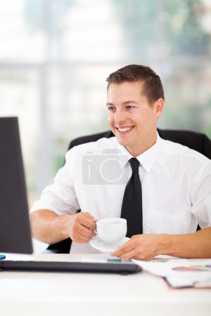 Photo for Cheerful businessman drinking coffee while working on his computer in office - Royalty Free Image