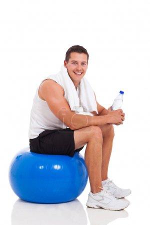 Photo pour Jeune homme assis sur le ballon de fitness après l'exercice - image libre de droit