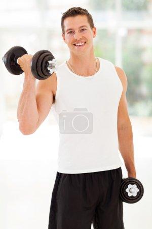 Photo pour Heureux jeune homme entraînement avec haltères à la salle de gym - image libre de droit