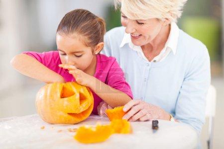 Granddaughter helping grandmother making halloween pumkin