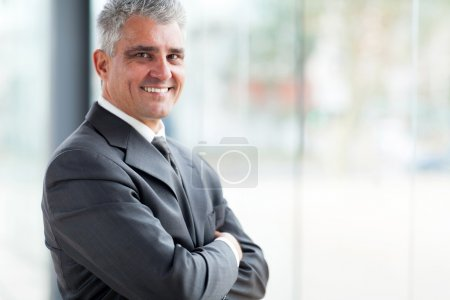 Photo for Cheerful businessman with arms folded looking at the camera - Royalty Free Image