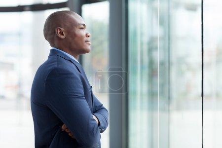 Foto de Considerado empresario africano con los brazos cruzados en oficina - Imagen libre de derechos