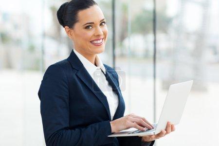 Beautiful business executive using laptop