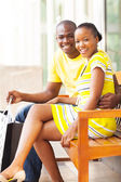 Young african couple sitting on public bench