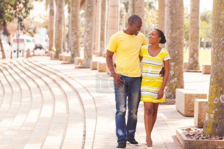 Foto de Alegre joven afro americano pareja caminando en la calle urbana - Imagen libre de derechos