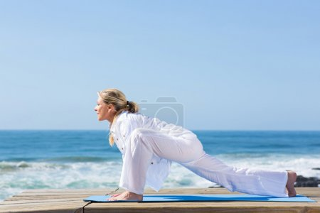 Senior woman working out at the beach