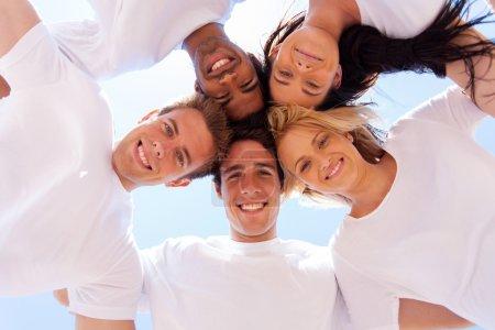 Photo pour Sous la vue du groupe d'amis dans un cercle regardant vers le bas - image libre de droit