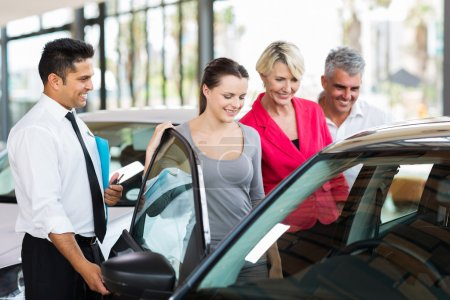 Photo for Handsome car salesman showing a new car to a family - Royalty Free Image