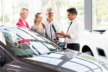Salesman showing car to family