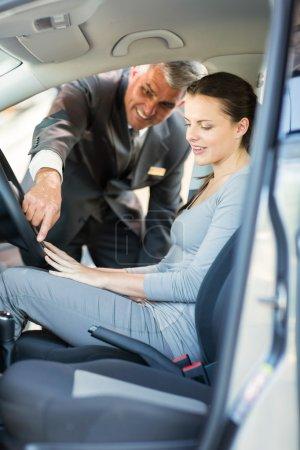 Middle age car salesman showing car