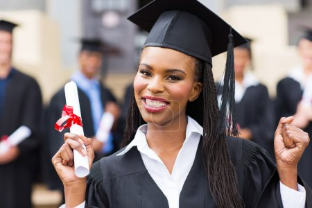 Photo for Happy african american female graduate with hands up with diploma at university graduation ceremony - Royalty Free Image