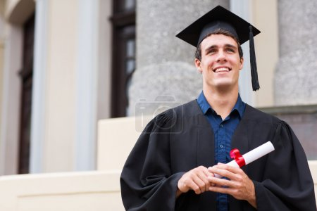 Graduate with diploma outside college building