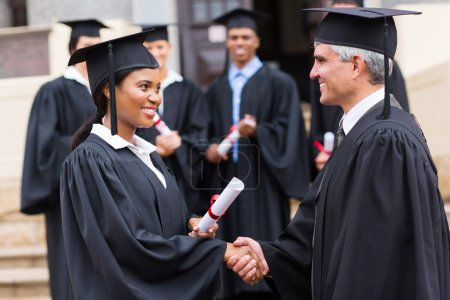 Afro american graduate handshaking with dean