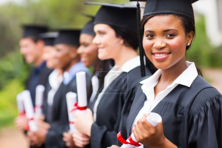 Photo for Pretty african female college graduate at graduation with classmates - Royalty Free Image
