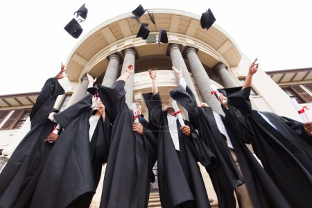 Photo for Group of happy graduates throwing graduation hats in the air - Royalty Free Image