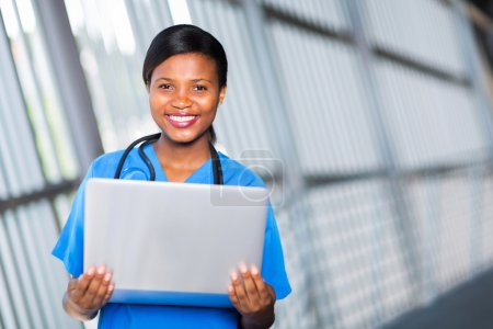 african american female doctor holding laptop computer