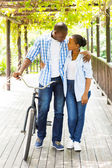 African couple walking with bike