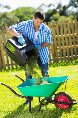 Man emptying lawnmower grass