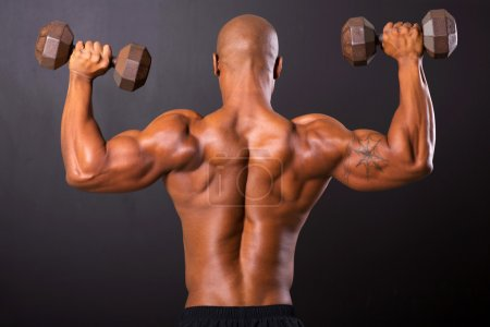 Photo for Rear view of african bodybuilder training with dumbbells - Royalty Free Image