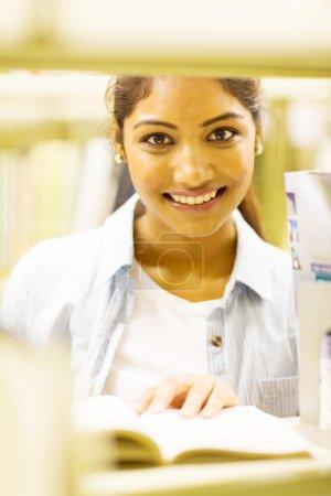 Mujer india estudiante detrás de estantería